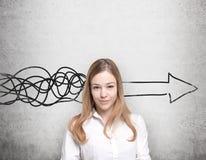 La bella donna sta pensando al concetto di sviluppo di affari Una freccia enorme è attinta il muro di cemento