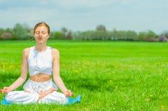 La bella donna sta praticando la seduta di yoga nella posa di Lotus su erba immagini stock libere da diritti