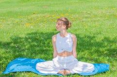La bella donna sta praticando la seduta di yoga nella posa di Lotus su erba immagini stock