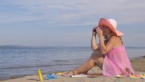 La bella donna sta riposando sulla spiaggia e sta esaminando il mare archivi video