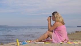 La bella donna sta riposando sulla spiaggia e sta esaminando il mare video d archivio