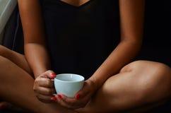 La bella donna sta sedendosi sul sofà, lei sta tenendo una tazza di caffè in sue mani fotografia stock