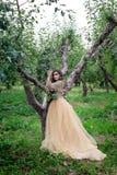 La bella donna sta stando fra il ramo dell'albero Fotografia Stock Libera da Diritti