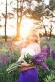 La bella donna sta stando ha circondato dal giacimento di fiori Fotografia Stock