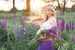 La bella donna sta stando ha circondato dal giacimento di fiori Immagine Stock Libera da Diritti