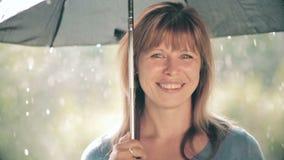 La bella donna sta stando sotto l'ombrello durante la pioggia e francamente sta sorridendo, godente della natura stock footage