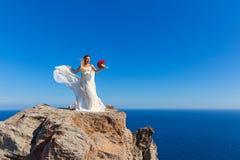 La bella donna sta su un'alta scogliera Immagini Stock Libere da Diritti