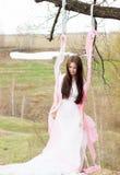La bella donna in tutto il vestito da sposa bianco il giorno soleggiato all'aperto oscilla Fotografia Stock