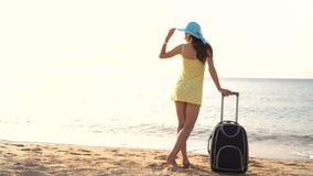 La bella donna in un cappello sta sulla spiaggia con una valigia e esamina la distanza video 4K stock footage