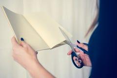 La bella donna in un vestito nero con un taccuino aperto con un paio di forbici taglia, studio isolato su fondo bianco Immagine Stock Libera da Diritti