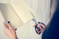 La bella donna in un vestito nero con un taccuino aperto con un paio di forbici taglia, studio isolato su fondo bianco Fotografie Stock Libere da Diritti