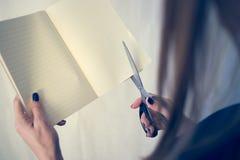La bella donna in un vestito nero con un taccuino aperto con un paio di forbici taglia, studio isolato su fondo bianco Fotografia Stock Libera da Diritti