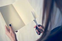 La bella donna in un vestito nero con un taccuino aperto con un paio di forbici taglia, studio isolato su fondo bianco Immagine Stock