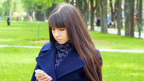 La bella donna utilizza lo smartphone delle cellule all'aperto nel parco - dettaglio La giovane ragazza felice attraente si rilas Immagini Stock