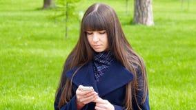 La bella donna utilizza lo smartphone delle cellule all'aperto nel parco - dettaglio La giovane ragazza felice attraente si rilas Fotografia Stock