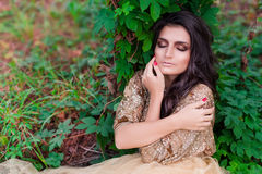La bella donna in vestito dall'oro è addormentata ed abbracciantesi Immagine Stock Libera da Diritti