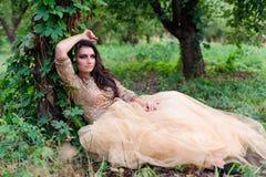 La bella donna in vestito dall'oro sta sedendosi appoggiandosi un albero Fotografie Stock Libere da Diritti