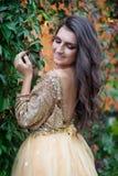 La bella donna in vestito dall'oro sta sorridendo Immagine Stock Libera da Diritti