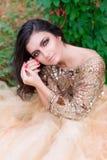 La bella donna in vestito dall'oro sta sorridendo Fotografie Stock