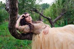 La bella donna in vestito dall'oro sta trovandosi sull'albero Immagini Stock Libere da Diritti