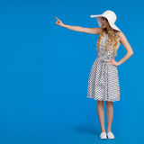 La bella donna in vestito e cappello punteggiati di Sun di bianco sta toccando Fotografie Stock Libere da Diritti