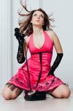 La bella donna in vestito rosa gode del telefono d'annata Fotografie Stock