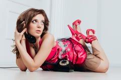 La bella donna in vestito rosa gode del telefono d'annata Fotografia Stock Libera da Diritti