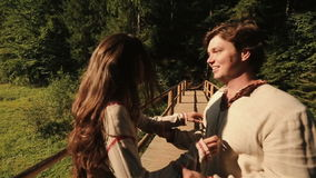 La bella e coppia felice balla sul ponte di legno Giovane e donna nell'amore su fondo di carpatico archivi video