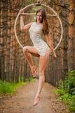 La bella e ginnasta aerea graziosa si esercita sull'anello dell'aria Immagini Stock