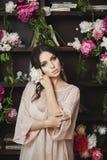 La bella e giovane donna di modello castana sexy, in vestito grigio, sta posando con i fiori in biblioteca immagine stock
