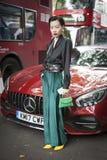 La bella e ragazza alla moda di A in una blusa nera, un verde ansima, orecchini d'annata del chanel che posano durante la settima immagine stock