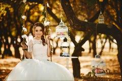 La bella e ragazza di modello castana alla moda in vestito alla moda dal pizzo di nozze si siede sulle oscillazioni d'attaccatura immagine stock