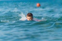 La bella fabbricazione del ragazzo spruzza in mezzo allo swimmin delle onde del mare Fotografia Stock