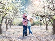 La bella famiglia felice cammina in giardini di fioritura fotografia stock