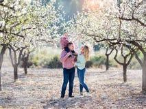 La bella famiglia felice cammina in giardini di fioritura fotografie stock