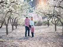La bella famiglia felice cammina in giardini di fioritura immagine stock libera da diritti