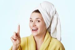 La bella femmina allegra sorridente applica la crema o la maschera sul fronte, essendo felice di comprare i nuovi cosmetici, annu Immagine Stock