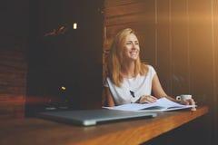 La bella femmina con il sorriso sveglio sta distogliendo lo sguardo mentre si rilassava dopo il lavoro sul suo computer portatile Fotografia Stock Libera da Diritti
