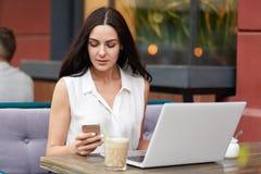 La bella femmina concentrata legge attentamente le informazioni sulla pagina Web tramite telefono cellulare, si siede davanti al  Fotografie Stock Libere da Diritti
