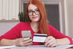 La bella femmina dai capelli rossi verifica l'equilibrio di conto della carta di credito sullo Smart Phone con l'applicazione mob immagine stock libera da diritti