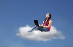 La bella femmina si siede sulla nuvola facendo uso del computer portatile Fotografie Stock