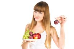 La bella frutta della stretta della ragazza sopra bianco Fotografia Stock