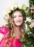 La bella giovane bionda con le gambe lunghe in un poco vestito rosso sulla corona capa dei fiori, corda ha avvolto la vite e l'ed Fotografie Stock Libere da Diritti