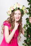 La bella giovane bionda con le gambe lunghe in un poco vestito rosso sulla corona capa dei fiori, corda ha avvolto la vite e l'ed Fotografie Stock