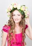 La bella giovane bionda con le gambe lunghe in un poco vestito rosso sulla corona capa dei fiori, corda ha avvolto la vite e l'ed Fotografia Stock Libera da Diritti