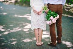 La bella giovane coppia alla moda che sta indietro, il tipo sta tenendo un mazzo delle peonie, le relazioni, la data, stile Fotografie Stock Libere da Diritti