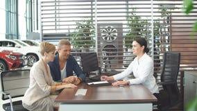 La bella giovane coppia firma i documenti all'ufficio del concessionario auto stock footage