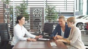 La bella giovane coppia firma i documenti all'ufficio del concessionario auto archivi video