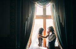 la bella giovane coppia, i costi vicino ad una finestra in un interno antico, lo sposo con la tenerezza e l'amore bacia il bride& fotografia stock libera da diritti