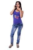 La bella giovane donna è sorpresa quando parla su un telefono cellulare isolato su fondo bianco Fotografia Stock